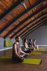Group of people practicing yoga in yoga studio