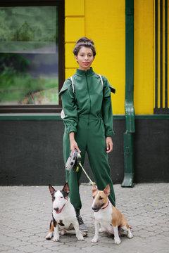 Fashion portrait of multiracial woman with pitbulls
