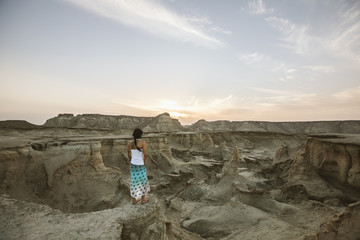 beautiful woman with skirt standing in rugged desert landscape at sunset, queshm island, iran