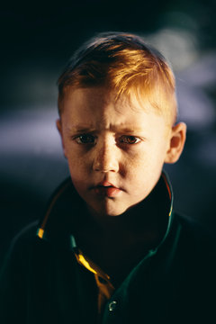 Portrait of boy with freckles standing outdoors