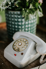 Old white rotary telephone on a table