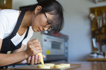 Young asian woman learning to make dessert in the kitchen