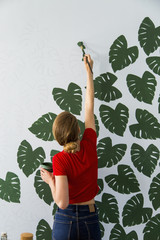 Woman painting flowers on wall