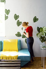 Woman drawing leaves on wall