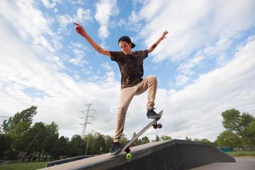 Teenager performing extreme skateboarding tricks on ramp railing