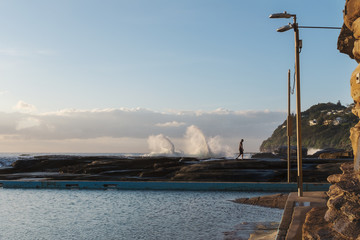 man taking early morning walk by the surf pool at Whale Beach, N