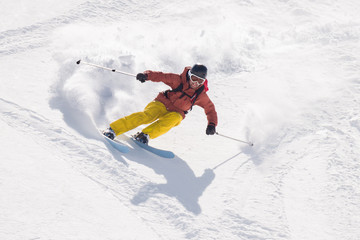 Man skiing with  speed downhill ski slope splattering the snow