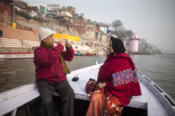 Senior couple travelling on boat and taking photograph