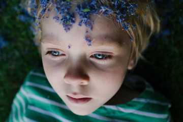 Little girl with Lilac petals on her head plays at dusk.