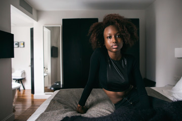 Portrait of Pretty Young African Readhead Sitting on Bed