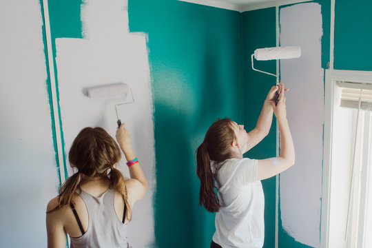 teenagers painting walls in a room