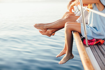 Family dangling Feet off Side of Sailboat