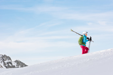 Woman ski touring on snowy plateau on a sunny day