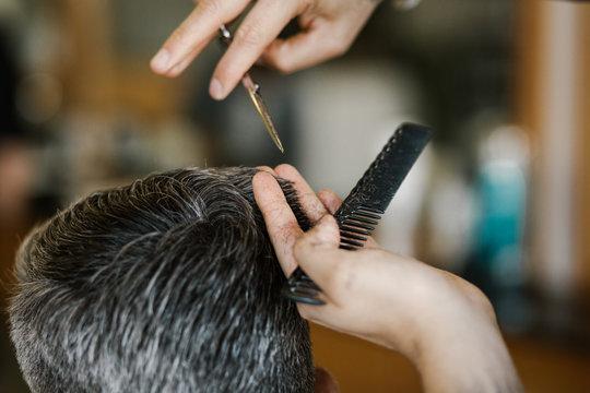 detail of barber trimming hair