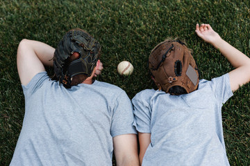 father and son take a break from playing catch in the backyard