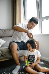 Father styling his daughter's hair at home