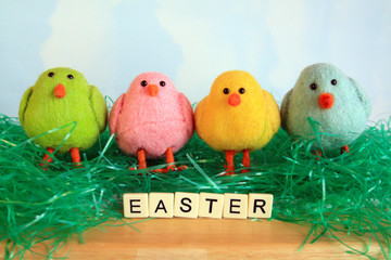 four colorful chicks with Easter grass with the word Easter letter tiles with sky background