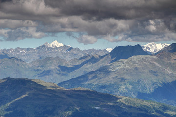 Gray clouds over sunlit snowcapped pointed Rotspitze Pizzo Rosso peak of Venediger Group and sharp Rote Spitze peak of Villgratner Berge in shadow, Deferegger Alpen Hohe Tauern Osttirol Austria Europe