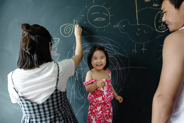 Toddler girl and her parents drawing on blackboard wall