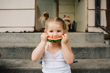 Toddler siblings eating fresh watermelon outside in early summer.