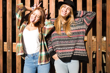 Beautiful two young women having fun in front of the rustic wood