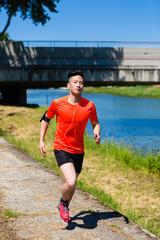 Teenage boy running on footpath near a river