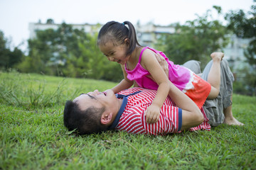 Asian man lying on lawn playing with his lovely little girl