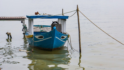 blue and white fishing boat  tied up at a pier on the river in Hoi An, Vietnam