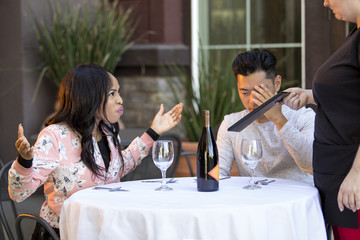 Couple on a date angry at a waitress in an outdoor restaurant.  They are upset and dissatisfied with the customer service or the food in the cafe.  The image depicts the food and service industry.