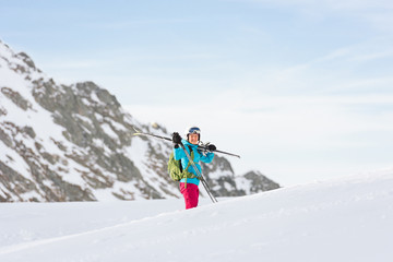 Female skier carrying her equipment on snowy mountain plateau