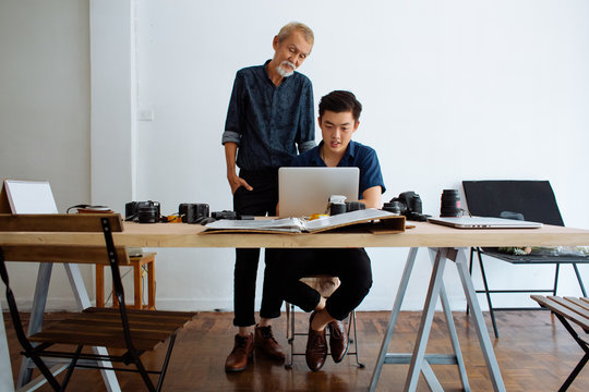 Senior man working together with young Asian designer
