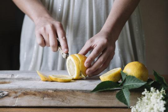 Crop woman cutting lemons