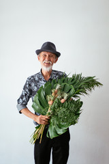 Happy asian old man holding tropical bouquet and mini pineapple