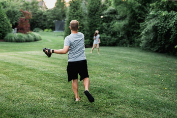 Father and son practicing catch with a baseball in the backyard
