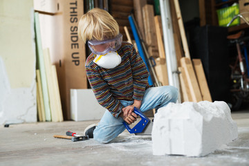 Boy in workshop using differnt tools for sculpting