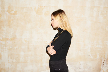 Side view of blonde girl embracing herself over shabby wall.