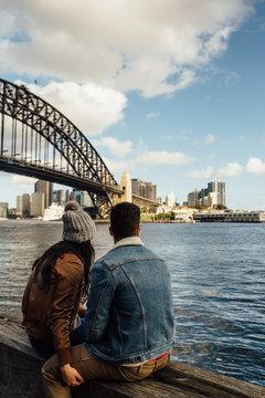 Tourist Couple Sit Near Harbor Bridge