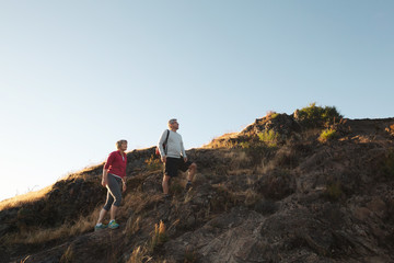 Fit, active middle age couple hiking together at sunset
