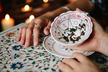 Woman fortune teller reading tea leaves