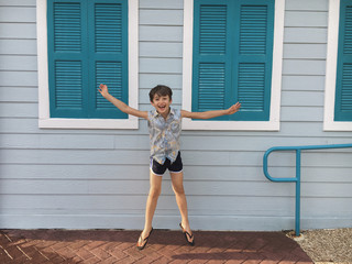 Laughing jumping Boy in Front of the Blue House