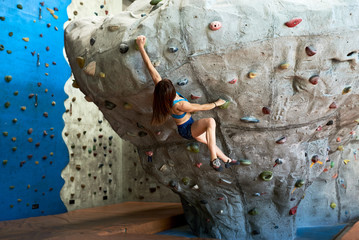 Athletic woman climbing artificial wall in gym.
