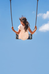 Girl sitting on a swing flying high in the blue sky