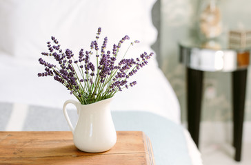 A white jug of lavender blooms in a bedroom.
