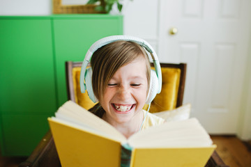 Young girl reading along while listening to a book