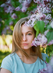 Portrait of young woman among lilac blossom