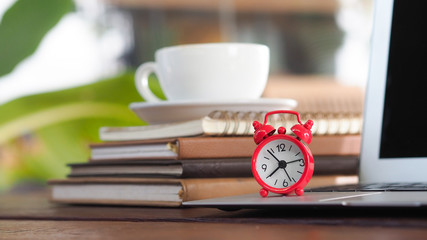 Workplace concepts, red color alarm clock with laptop computer and book stack and coffee cup on wooden desk, selective focus for business and education background