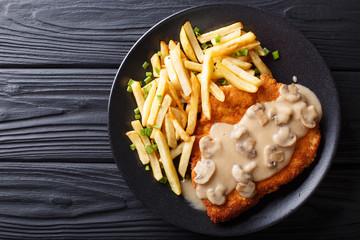 delicious Wiener Hunter schnitzel with sauce and french fries close-up. horizontal top view