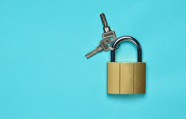 Golden closed lock with keys on a blue background. Copy space. Top View.