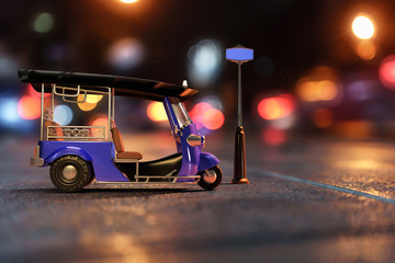 3D rendering composite with a photograph of Tuk Tuk in side view, Thai traditional taxi for public transportation with sign pole in a night scene with multicolor bokeh background.