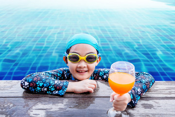 Happy Children at the Swimming Pool Side, Girl Relaxing with Summer Drink, Smile and Looking at Camera, Blue Water as background
